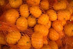 Orangen verpackt in der roten Filetarbeit lizenzfreies stockbild