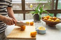 Orangen werden eigenhändig zusammengedrückt, um einen reinen und gesunden Orangensaft zu machen Stockbild
