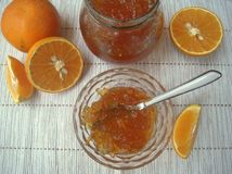 Orangenmarmelade und frische Orangen auf dem Tisch Stockfotos