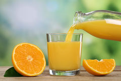 Orangensaft, der in ein Glas im Sommer gießt Lizenzfreies Stockfoto