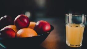 Orangensaft der Frucht in einem Glas und in den Früchten auf einer Tabelle stock video