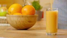 Orangensaft, der in Glas gießt stock footage