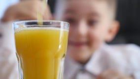 Orangensaft, der in Glas gießt Hintergrund des kleinen Jungen Selektiver Fokus stock video
