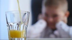 Orangensaft, der in Glas gießt Hintergrund des kleinen Jungen Selektiver Fokus stock footage