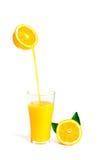 Orangensaft, der in Glas mit orange Scheibe und Blatt, Isolator gießt Lizenzfreie Stockfotos