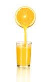 Orangensaft, der in Glas von der Hälfte der Orange gießt Stockfotos