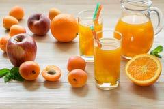 Orangensaft des Aprikosenpfirsichapfels mit Eis Stockfotos