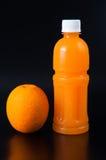 Orangensaft in einer Flasche und in einer Orange nahe bei ihr auf Schwarzem Stockfoto