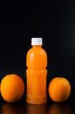 Orangensaft in einer Flasche und in einer Orange nahe bei ihr auf Schwarzem Lizenzfreie Stockfotos