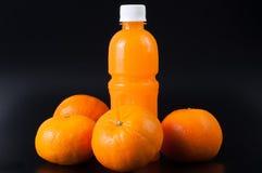 Orangensaft in einer Flasche und in einer Orange auf Schwarzem Lizenzfreie Stockfotografie