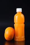 Orangensaft in einer Flasche und in einer Orange auf Schwarzem Lizenzfreie Stockfotos