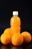 Orangensaft in einer Flasche und in einer Orange auf Schwarzem Stockfotos