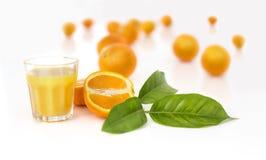 Orangensaft mit Orangen und Blättern im Hintergrund. Lizenzfreie Stockbilder