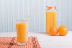 Orangensaft neben köstlichen reifen Orangen auf dem Tisch Stockbilder