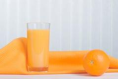 Orangensaft neben köstlichen reifen Orangen auf dem Tisch Lizenzfreies Stockbild