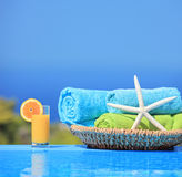 Orangensaft, Starfish und Tücher nahe bei einem Pool Lizenzfreie Stockfotos