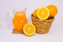 Orangensaft und Orange auf weißem Hintergrund Lizenzfreie Stockfotos