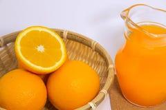 Orangensaft und Orange auf weißem Hintergrund Lizenzfreie Stockbilder