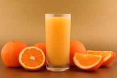 Orangensaft und reife Orangen Stockfotos