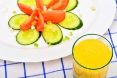 Orangensaft und Salat mit Tomate, Gurke Stockfotografie