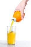 Orangensaft wird in ein Glas der Orange gegossen Stockfotografie