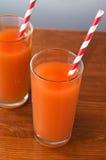 Orangensaftglas und frische Orangen auf Holz Lizenzfreie Stockbilder