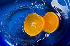 Orangenspritzen im Wasserblauhintergrund Stockfoto