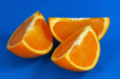 Oranges 01. Orange Wedges Over Blue Background royalty free stock image