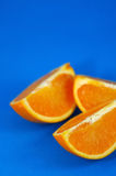Oranges 02. Orange Wedges Over Blue Background. Shallow DOF royalty free stock images