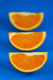 Oranges 06. Orange Wedges Over Blue Background. Shallow DOF royalty free stock photo