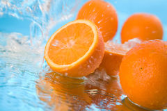 Oranges. In a fountain of water on a dark blue background stock photos
