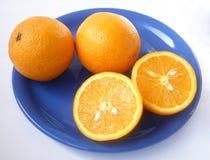 Oranges. Oranges on a dark blue plate Stock Photos