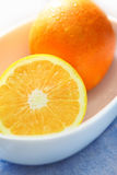 Oranges. In white bowl with table setting Stock Image