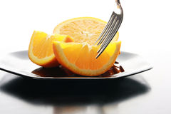Oranges. A beautiful and juicy orange cut up on a plate being eaten with a silver fork Royalty Free Stock Photo