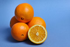Oranges. Three and half oranges on blue background Royalty Free Stock Images