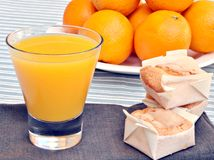 Oranges. Orange juice with three biscuits on cloth in the back some oranges stacked next to each other royalty free stock images