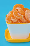 Oranges. Peeled oranges in a cup on blue background Royalty Free Stock Image