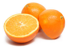 Oranges. An orange cut in half with a whole orange on white background Stock Photography