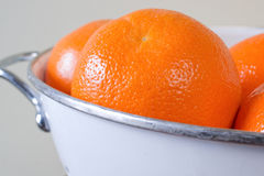 Oranges. In white colander against beige background royalty free stock image