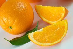 Oranges. Two slices of fresh orange and whole orange with green leaf Royalty Free Stock Photos