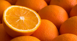 Oranges. Background of oranges with one fruit cut half Stock Photography