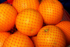 Oranges. In a red pastic mesh Royalty Free Stock Images