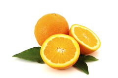 Oranges. With leafs, one orange cut in two, on white background stock photos