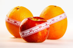 Oranges and apple with tailor's ruler. Fruit healthy vitamin diet Stock Image