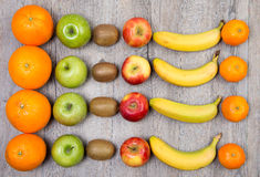 Oranges, apples, kiwis and bananas. Placed on a wooden table stock photo