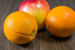 Oranges and apples. Oranges and apples pile on wooden floor royalty free stock photo