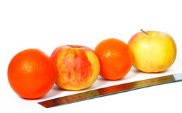 Oranges and apples in a row and ruler. On a white background Royalty Free Stock Photos