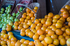 Oranges and apples spilling from baskets outside a Paris market Stock Images