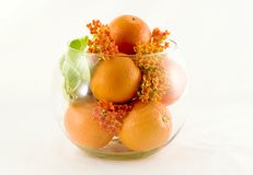 Oranges as a center piece. Fill a bowl full of oranges, pick some flowers from the garden and combine them for an attractive center piece Royalty Free Stock Photos