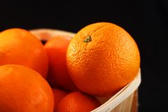 Oranges in a basket. On a black background royalty free stock images